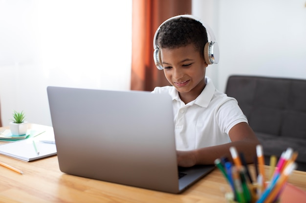 Kleiner junge, der seinem lehrer über kopfhörer zuhört