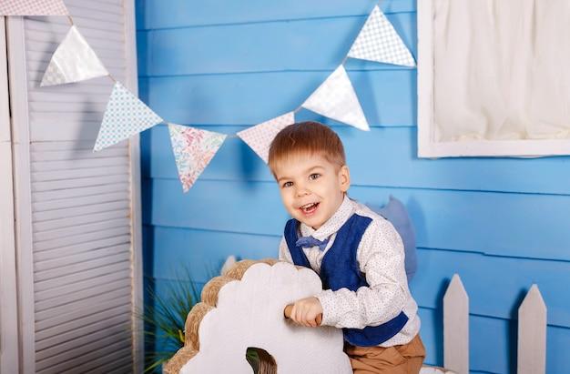 Kleiner junge, der seinen geburtstag feiert. geburtstagsfeier für süßes kind. überraschtes kind, das kamera auf blaue wand betrachtet. spaß, freude, feier und urlaub. trendige kinderkleidung, partykonzept