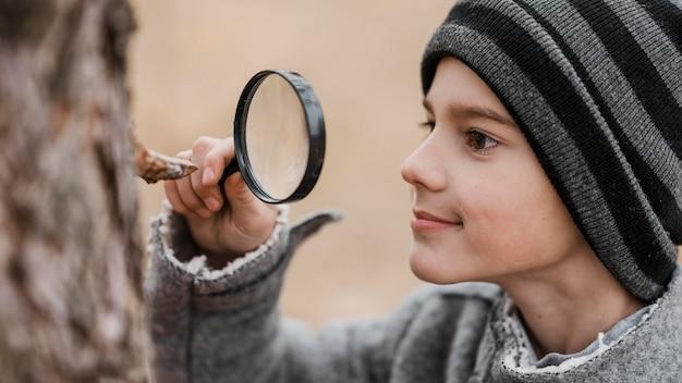 Kleiner junge der seitenansicht, der durch eine lupe schaut