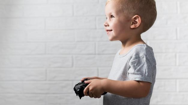 Kleiner junge der seitenansicht, der mit einem prüfer spielt