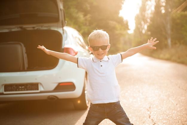 Kleiner junge, der sich ausruht und spaß am straßenrand auf einem roadtrip hat. roadtrip mit kinderkonzept.