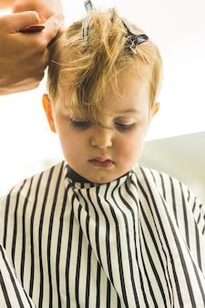 Kleiner junge, der sich die haare schneiden lässt