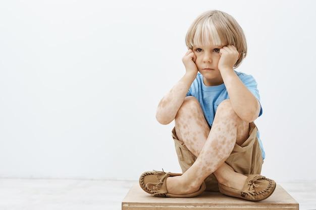 Kleiner junge, der sich düster fühlt, nicht wie jedes andere kind zu sein. unglückliches niedliches blondes kind, das mit gekreuzten füßen auf boden sitzt, hände auf gesicht hält und beiseite schaut