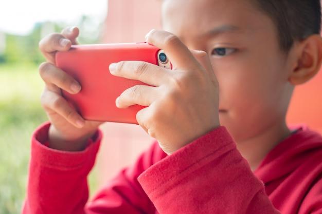 Kleiner junge, der smartphone in der horizontalen position hält