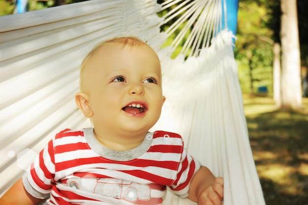 Kleiner junge, der sommer in der hängematte genießt