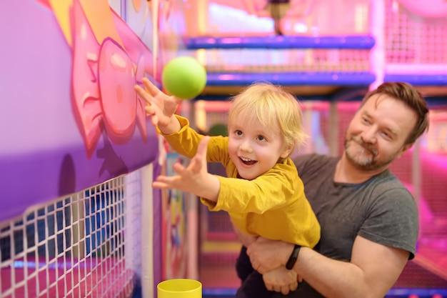Kleiner junge, der spaß am vergnügen im spielzentrum hat. kind spielt mit magischem ball.