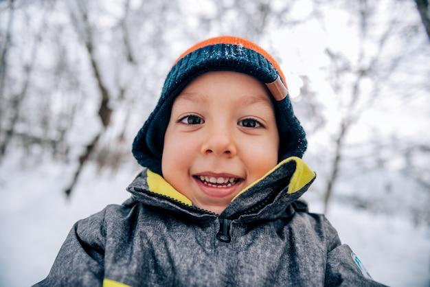 Kleiner junge, der spaß auf schnee hat