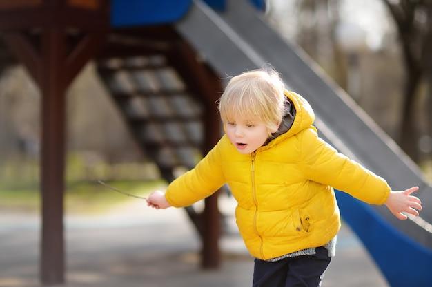 Kleiner junge, der spaß auf spielplatz im freien am frühlings- oder falltag hat