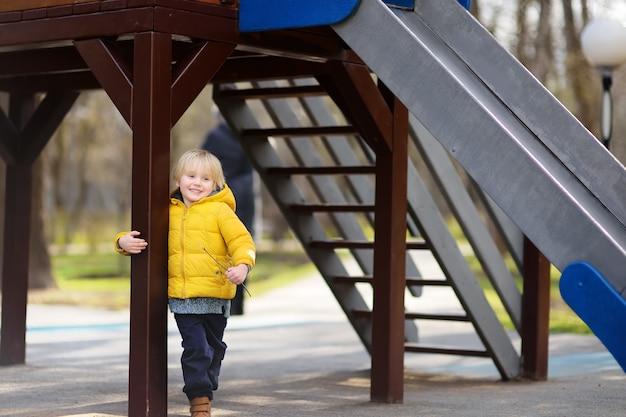 Kleiner junge, der spaß auf spielplatz im freien am frühlings- oder herbsttag hat