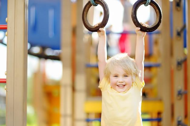 Kleiner junge, der spaß auf spielplatz im freien hat. sommer aktiv sport freizeit für kinder