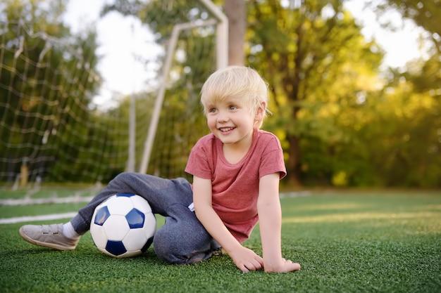 Kleiner junge, der spaß hat, ein fußball- / fußballspiel am sommertag zu spielen.