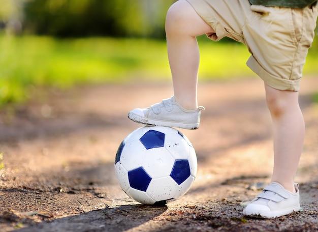 Kleiner junge, der spaß hat, ein fußball- / fußballspiel am sommertag zu spielen