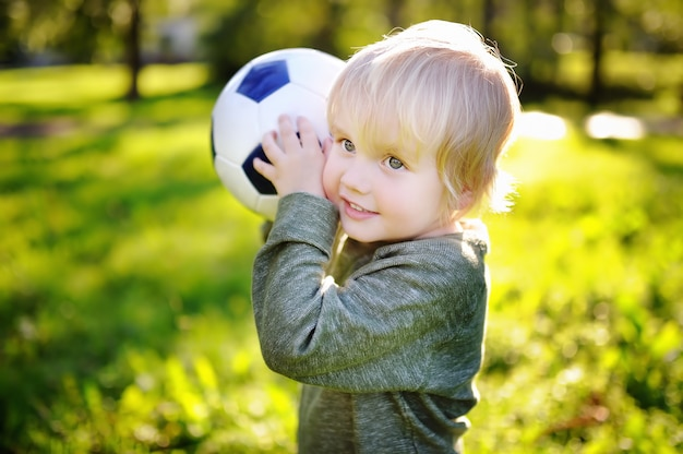 Kleiner junge, der spaß hat, ein fußballspiel am sonnigen sommertag zu spielen