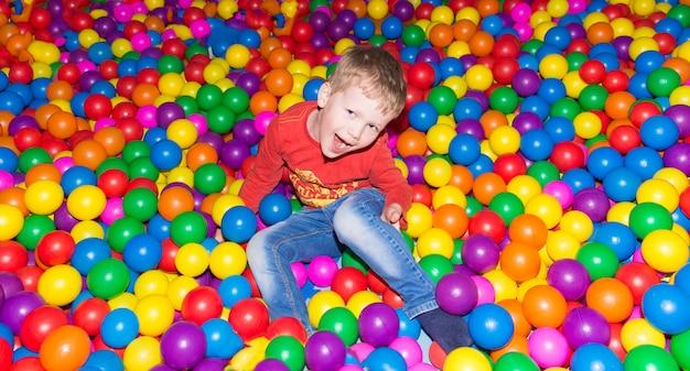 Kleiner junge, der spaß in einem pool von bunten bällen im unterhaltungszentrum hat