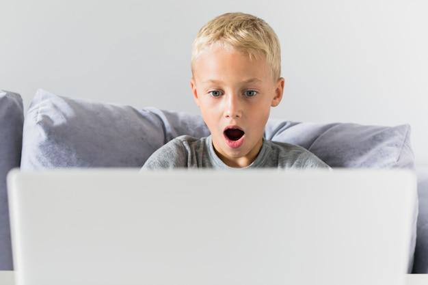 Kleiner junge, der spaß mit laptop hat