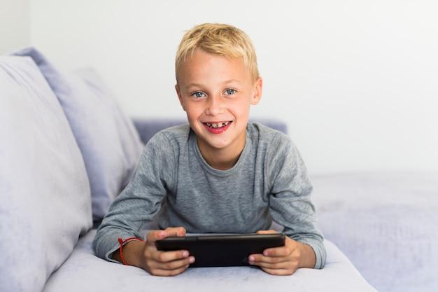 Kleiner junge, der spaß mit tablette hat