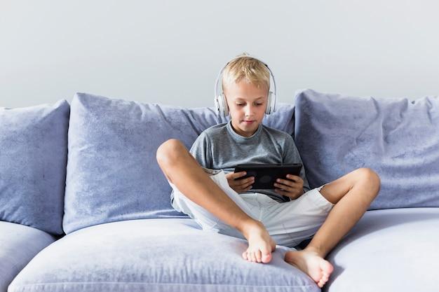 Kleiner junge, der spaß mit tablette und kopfhörern hat