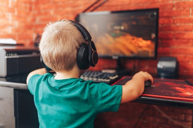 Kleiner junge, der spiele auf computer in den kopfhörern mit mikrofon, computerspiel spielt
