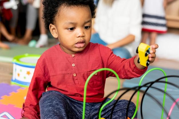 Kleiner junge, der spielwaren im spielzimmer spielt