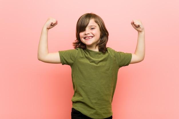 Kleiner junge, der stärkegeste mit den armen, symbol der weiblichen energie zeigt