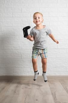 Kleiner junge, der steuerknüppel und das springen hält