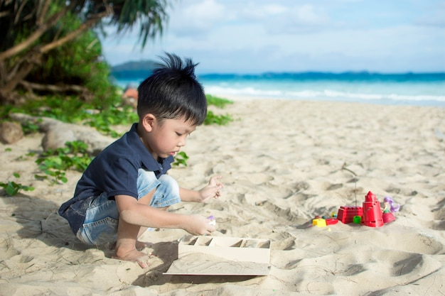Kleiner junge, der strandspielzeug auf dem sandstrand spielt