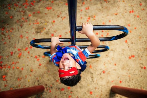 Kleiner junge, der superheld am spielplatz spielt