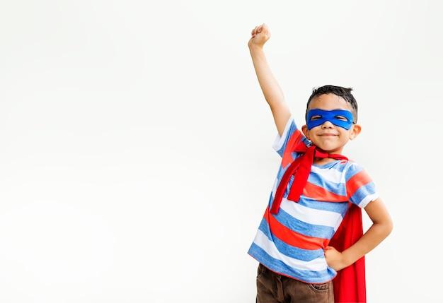 Kleiner junge, der superhelden am spielplatz spielt