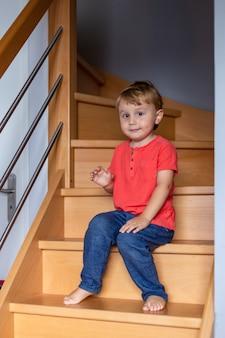 Kleiner junge, der t-shirt schwärmt, sitzt zu hause auf der treppe. barfuß kind. sicherheitshaus für kinder.