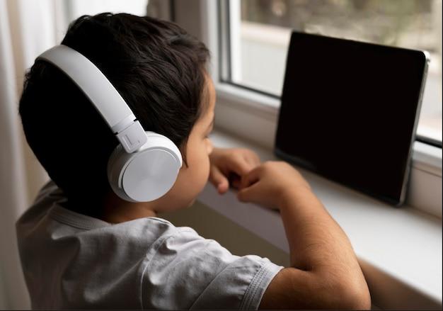 Kleiner junge, der tablett mit kopfhörern benutzt