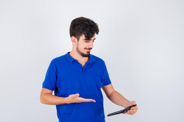 Kleiner junge, der taschenrechner hält und darauf im blauen t-shirt zeigt und glücklich aussieht. vorderansicht.