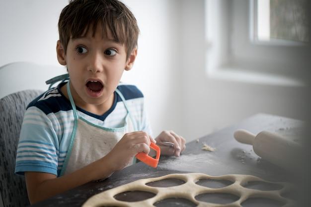 Kleiner junge, der teig für köstlichen bonbon macht