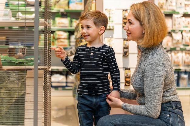 Kleiner junge, der tierhandlungsprodukte prüft