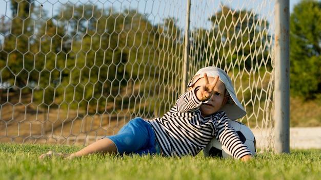 Kleiner junge, der über torpfosten auf einem sportspielfeld liegt, während sein fußball mit seinen fingern ein siegeszeichen gibt