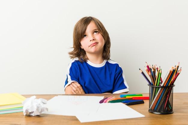 Kleiner junge, der unglücklich hausaufgaben auf seinem schreibtisch malt und tut.