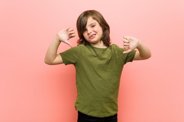 Kleiner junge, der unten daumen zeigt und abneigung ausdrückt.