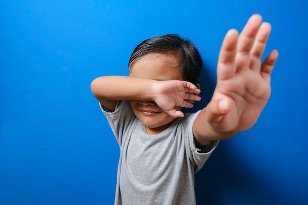 Kleiner junge, der unter mobbing leidet, hebt ihre handfläche und bittet darum, die gewalt zu stoppen