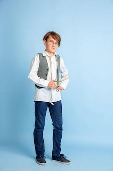 Kleiner junge, der vom zukünftigen beruf der näherin träumt. kindheits-, bildungs- und traumkonzept. will erfolgreicher mitarbeiter in der mode- und stilbranche werden, macht atelier kleidung. copyspace.