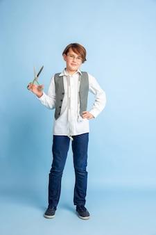 Kleiner junge, der vom zukünftigen beruf der näherin träumt. kindheits-, bildungs- und traumkonzept.