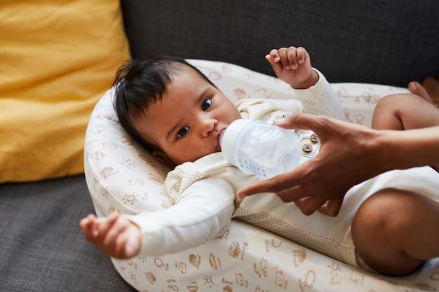 Kleiner junge, der von babyflasche trinkt