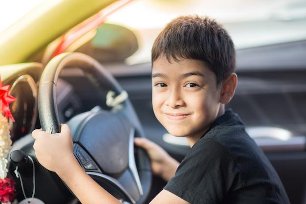 Kleiner junge, der vor dem auto hält lenkrad sitzt