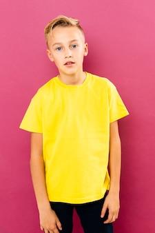 Kleiner junge der vorderansicht, der auf rosa hintergrund aufwirft