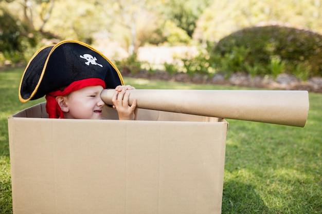 Kleiner junge, der vortäuscht, ein pirat zu sein und durch ein teleskop schaut