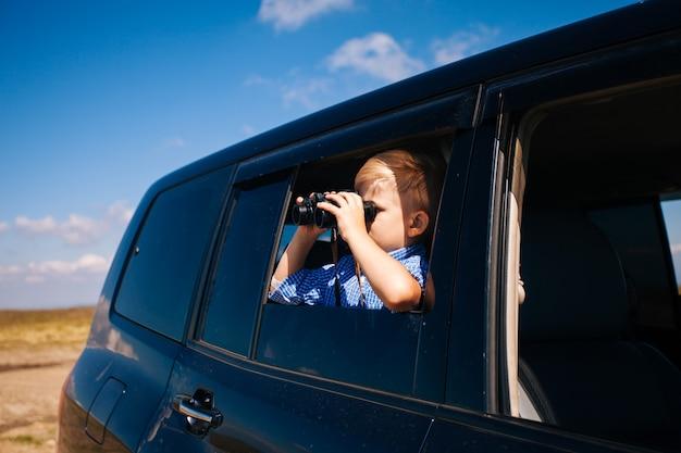 Kleiner junge, der während der fahrt mit dem auto durch ein fernglas schaut