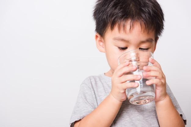 Kleiner junge, der wasser aus glas trinkt
