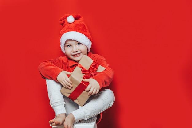 Kleiner junge, der weihnachtsgeschenk hält