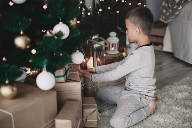 Kleiner junge, der weihnachtsgeschenke arrangiert