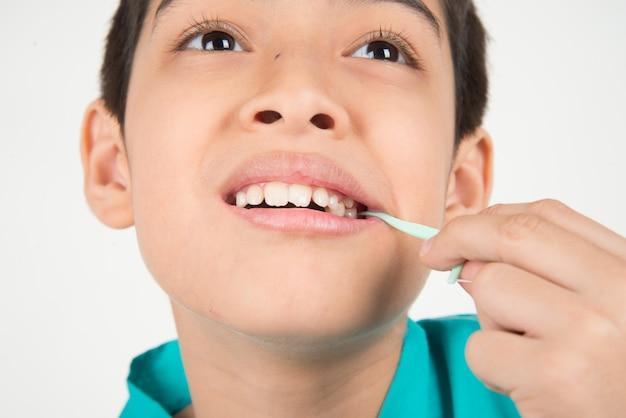 Kleiner junge, der zahnseide verwendet, um zahn zu säubern