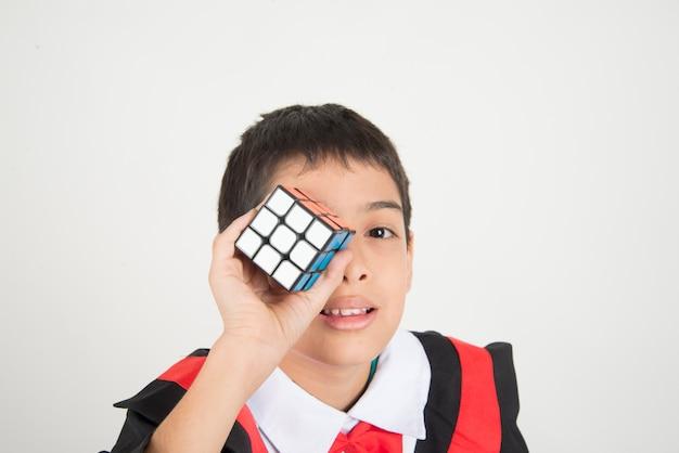 Kleiner junge, der zauberwürfel spielt