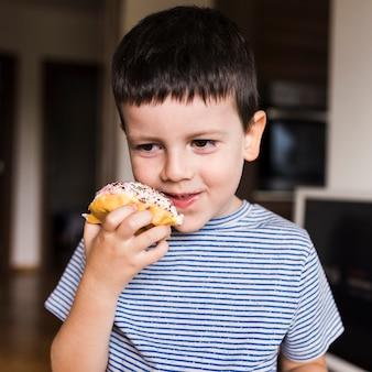 Kleiner junge, der zu hause doughnout genießt
